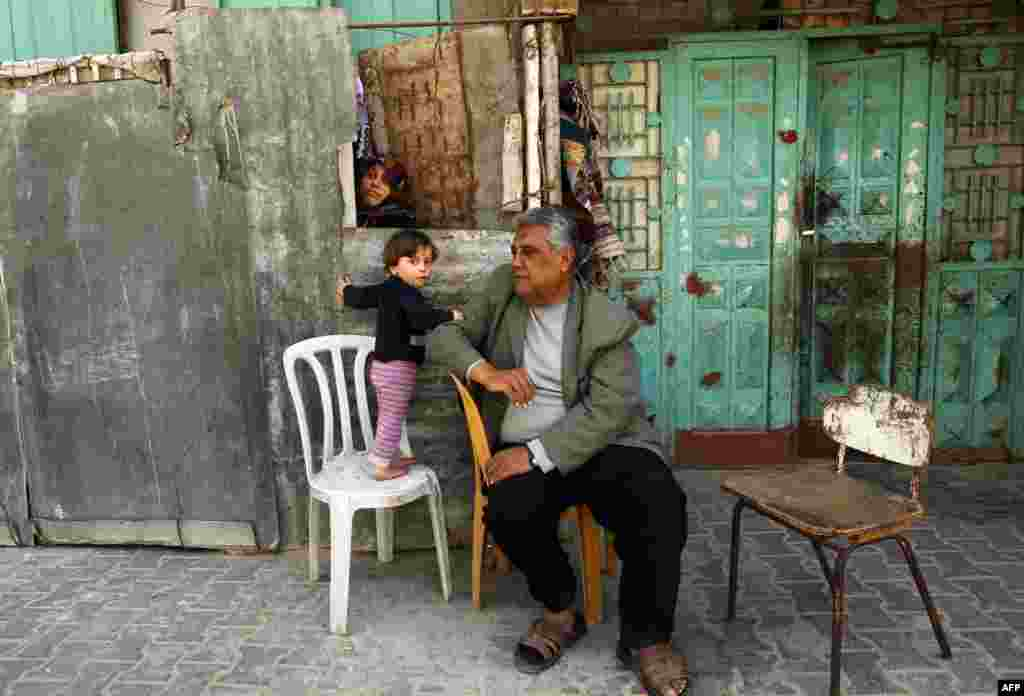 A Palestinian family sit outside their home in the Jabalia refugee camp in the northern Gaza Strip on April 6. (AFP/Mohammed Abed)
