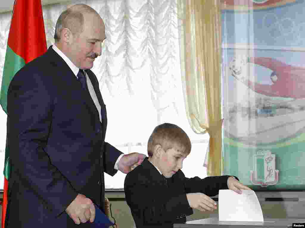 Lukashenka stands next to Kolya as he casts his ballot for president for him at a polling station in December 2010.