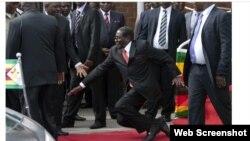 Зимбабвенің 90 жастағы президенті Роберт Мугабенің өз жақтастары алдында сөз сөйлегеннен кейін құлап бара жатқан сәті. Видеодан скриншот. Хараре, 5 ақпан 2015 жыл.
