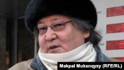 Театральный режиссер Болат Атабаев перед зданием банка дает интервью журналистам. Алматы, 8 февраля 2012 года.