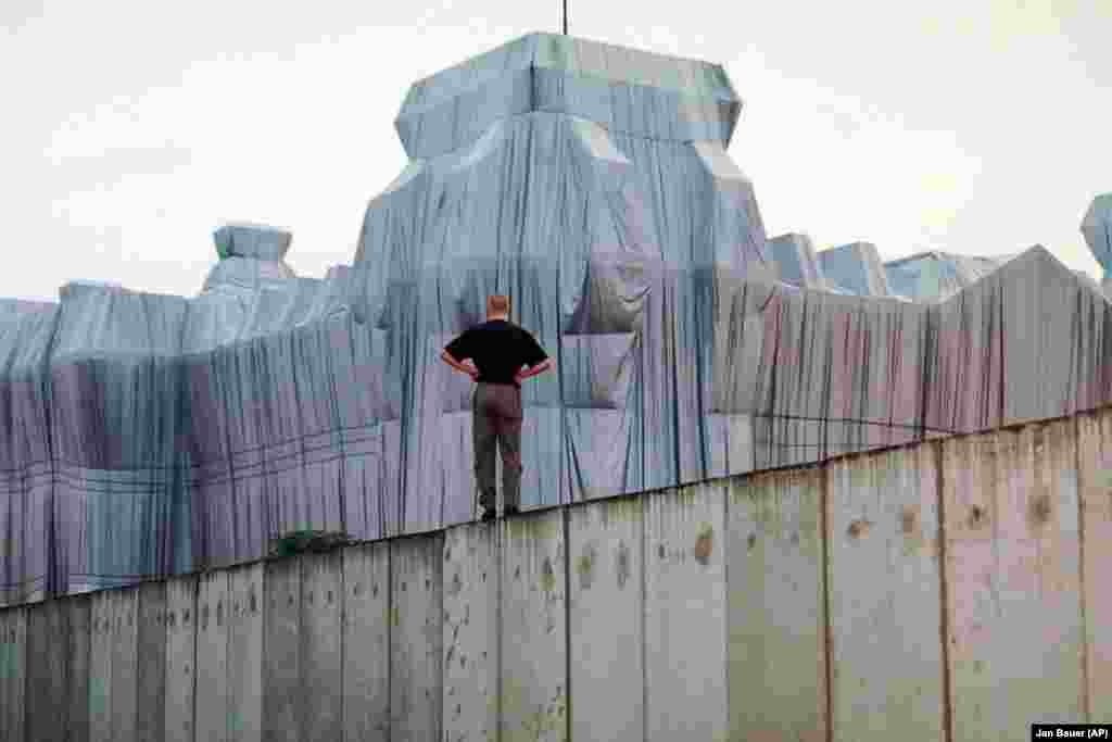 A man stands atop the remains of the Berlin Wall and looks at the wrapped Reichstag building in June 1995.