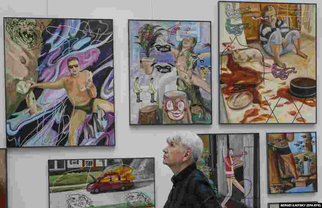 A visitor examines artworks by Ivan Gorshkov of Russia.