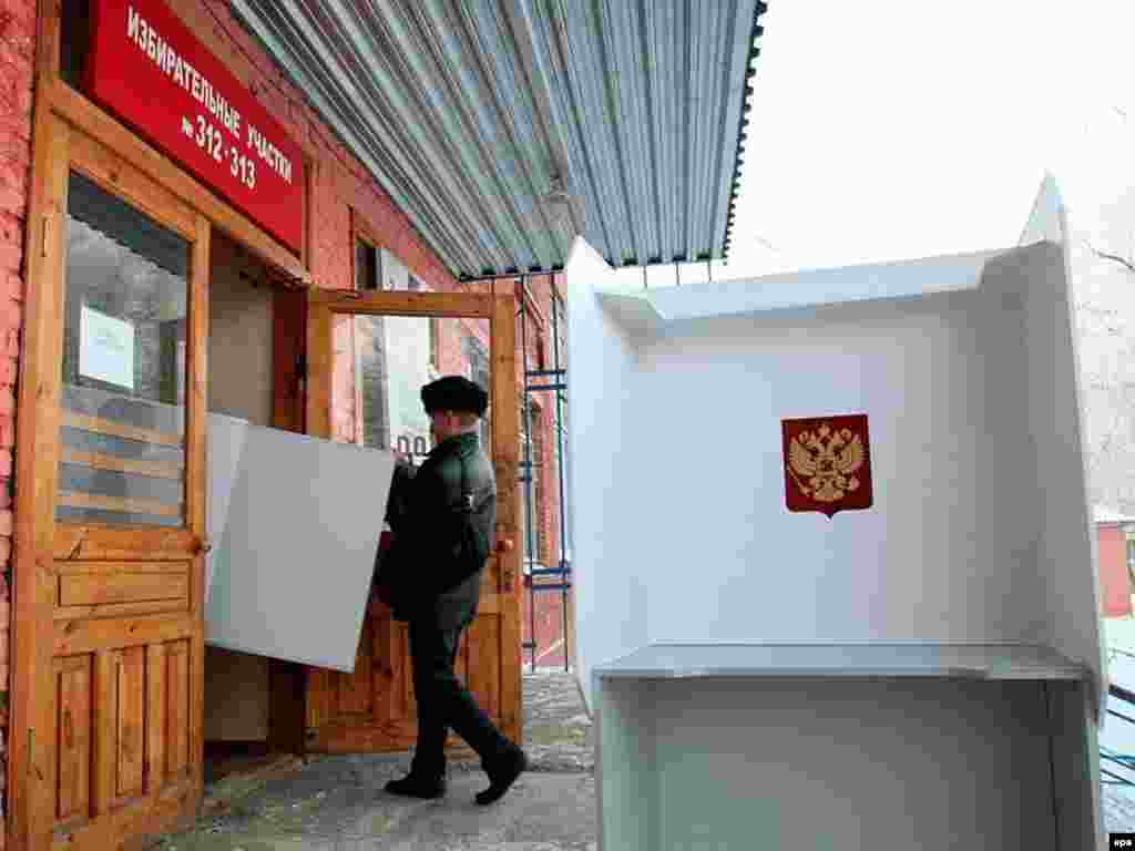 Russians went to the polls today across 11 timezones to vote for a new parliament. Members of the local election commission prepare the polling station in the western Siberian city of Kemerovo.