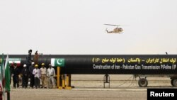 Workers stand by as a security helicopter lands near the pipeline during a ground-breaking ceremony to mark the inauguration of the Iran-Pakistan gas pipeline, in the city of Chahbahar, in March.