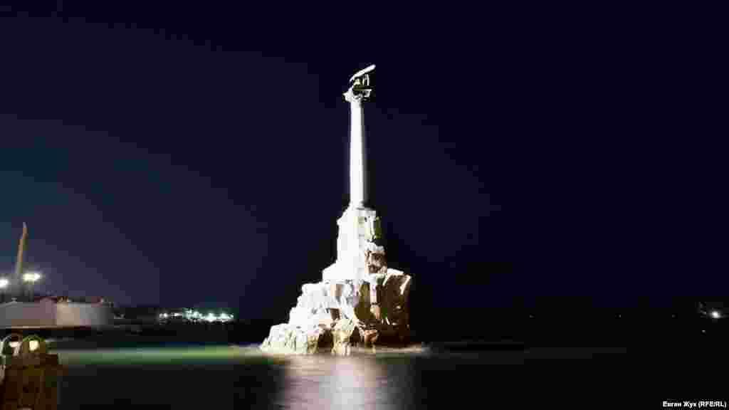 Штиль в Севастопольской бухте и памятник затопленным кораблям в лучах прожекторов