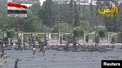 Army personnel run to the scene of the suicide attack in Yemen's capital Sanaa on May 21.