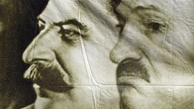 A poster with portraits of Josef Stalin (left) and Alyaksandr Lukashenka seen at a protest rally in May.