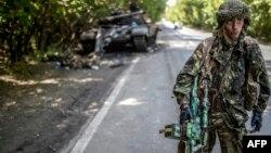 Бойовик угрупування «ДНР» біля знищеного танка українських військ, 22 липня 2014 року
