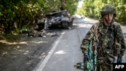 Separatist pro-rus lângă un tanc ucrainean distrus, la nord de Doneţk