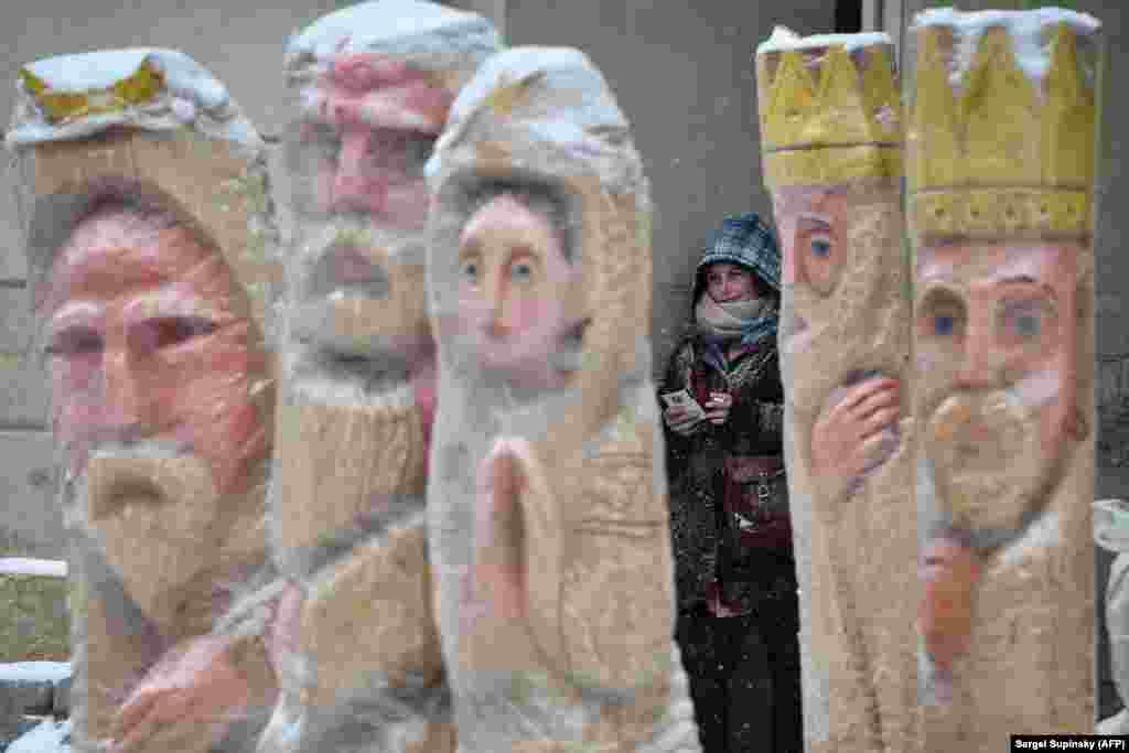 A girl takes a break behind sculptures depicting the Nativity in the center of western Ukrainian city of Lviv. (AFP/Sergei Supinsky)