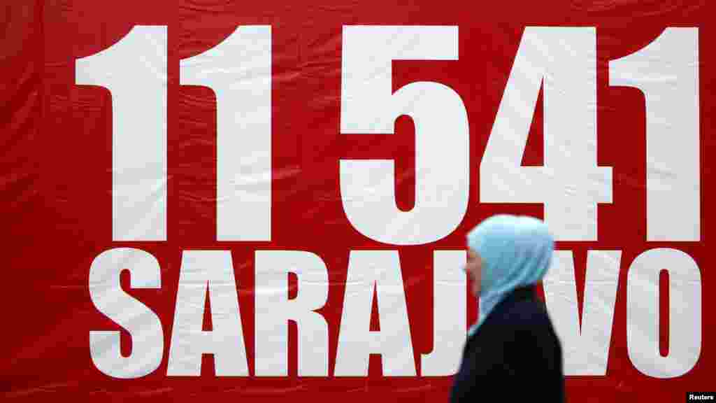 A Bosnian Muslim woman walks near a banner with the number 11,541 -- the number of Sarajevans killed in the 44-month siege.