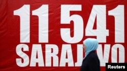 Мусульманка проходит мимо баннера с цифрой 11 541 - число погибших в результате осады Сараево. 6 апреля 2012 года.