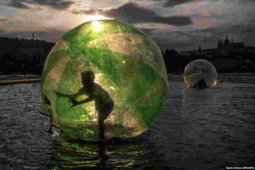A boy goes zorbing on the Vltava River during a warm summer's day in Prague. (epa-EFE/Martin Divisek)