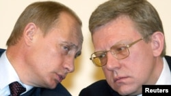President Vladimir Putin (left) and Finance Minister Aleksei Kudrin speak to each other during a meeting of economy ministers in Moscow in March 2004.