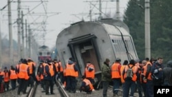 Workers prepare to remove a derailed car of the Nevsky Express.