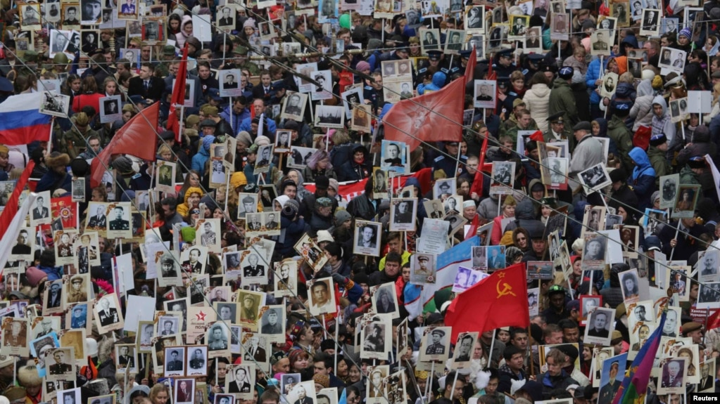 People carry pictures of World War II soldiers as they take part in the Immortal Regiment march during the Victory Day celebrations in central St. Petersburg on May 9.