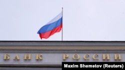 A Russian flag flies over the headquarters of the country's central bank in Moscow (file photo)