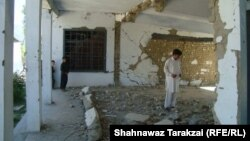 Locals and students inspect the ruins of a government girls high school destroyed by the Taliban in Bajaur Agency in June.