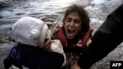 A woman falls into the water with her child as they disembark from a dinghy as refugees and migrants arrive at the Greek island of Lesbos after crossing the Aegean sea from Turkey earlier this month.