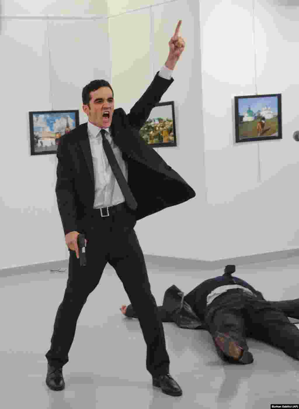 "An off-duty Turkish police officer, Mevlut Mert Altintas, shouts ""Don't forget Aleppo!"" moments after he shot and killed the Russian ambassador to Turkey, Andrei Karlov, at a photo exhibition in Ankara on December 19. Altintas was later killed by police in a shoot-out. (AP/Burhan Ozbilici)"