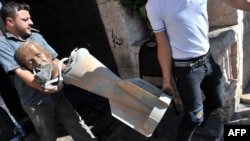 Rebel fighters carry the head of a statue of late President Hafez al-Assad, with a shoe glued to his mouth, along with what appears to be a cluster bomb, which they accuse government forces of using in attacks on rebel-held areas.