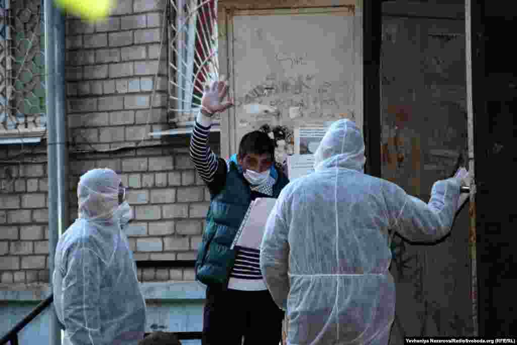 Медпрацівники розмовляють з одним із мешканців гуртожитку в Запоріжжі, в якому виявили COVID-19