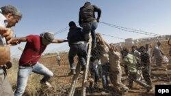 """محتجون كرد أتراك يحطمون سياجاً على الحدود السورية خلال إحتجاجات ضد عنف مسلحي تنظيم """"داعش"""" الموجه نحو الكرد السوريين"""