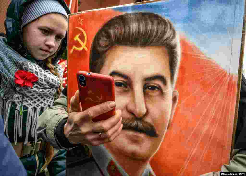A woman, next to a girl, holds a portrait of former Soviet dictator Josef Stalin and takes a selfie at his grave outside the Kremlin on Red Square in Moscow on March 5 as members of different communist and leftist movements gathered to mark the 66th anniversary of Stalin's death. (AFP/Mladen Antonov)