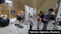 Відвідувачі розглядають експонати в «Парку корупції», який зроблений у формі гігантського намету за мотивами сумновідомого «Золотого батону». Травень 2018 року