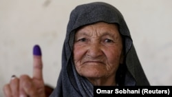 An Afghan woman shows proof of her vote after casting a ballot in Kabul on September 28.