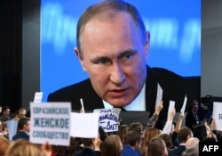 A video screen shows Putin speaking during his annual press conference last year while journalists hold up signs showing their media affiliations.