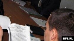 Лаңкестік жиһадшылар тобын құрмақшы болды деген айып тағылған Қуат Жобалаев сот залында өзіне қарсы тергеу ісімен танысып отыр. Астана, 11 қыркүйек 2009 жыл.