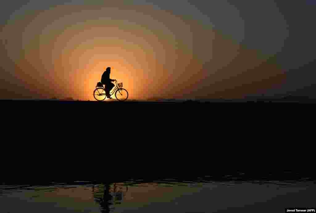 An Afghan man rides a bicycle along a road at sunset in the Arghandab district of Kandahar Province. (AFP/Javed Tanveer)
