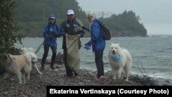 Волонтеры с собаками на берегу Байкала во время экологической операции
