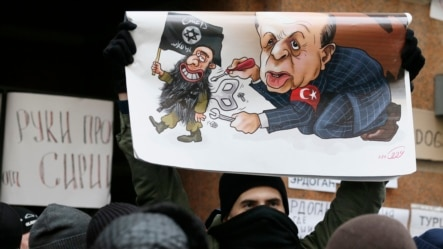 A Russian protester holds a placard showing Turkish President Recep Tayyip Erdogan as a puppet of Islamic State during a rally in front of Turkish Embassy in Moscow on November 25.