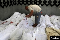 A man searches for the bodies of his relatives at a field hospital near the site of clashes between pro-Morsi activists and police east of Cairo.