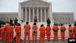 Участники акции протеста, одетые в тюремную робу, выступают перед зданием Верховного суда США с требованием закрыть тюрьму Гуантанамо. Вашингтон, 11 января 2013 года.