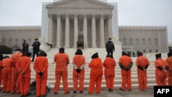 Hooded demonstrators take part in a rally in January in front of the U.S. Supreme Court on Capitol Hill in Washington to call for the closing of the Guantanamo Bay detention center.
