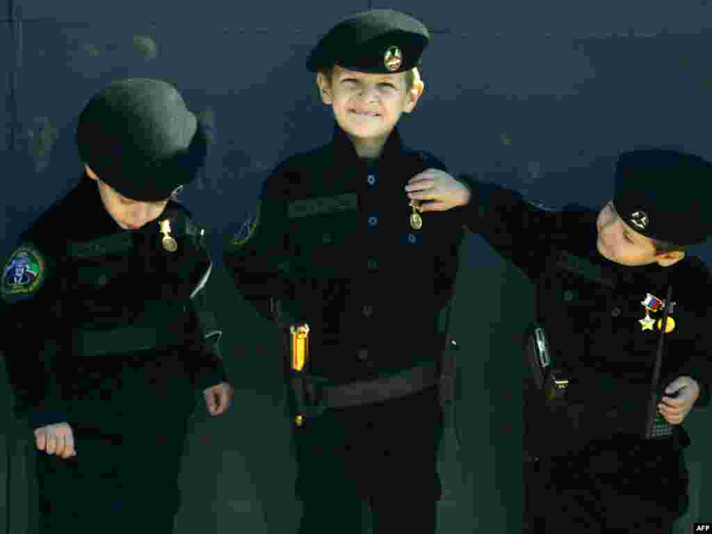 A Chechen boy wears a military uniform decorated with medals at an award ceremony of officers and soldiers of special police forces who distinguished themselves in defense of the parliament building during an attack by a group of militants on October 19, at the parade ground of cadet corps in Grozny on November 3.Photo by Viskham Magomadov for AFP