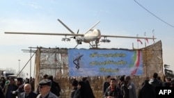 Iranians walk past Iran's Shahed 129 drone displayed during celebrations, February 11, 2016