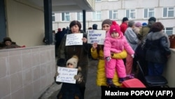 "Local residents hold signs, with one reading ""Don't kill our kids!"" as they gather outside the hospital in Volokolamsk on March 21."