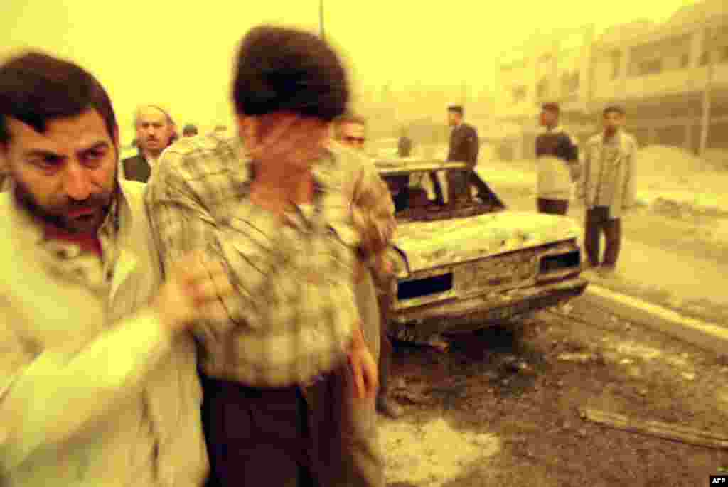 An Iraqi comforts a friend after missiles struck a Baghdad market, killing at least 14 people on March 26, 2003.