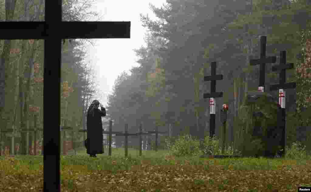 A woman prays in front of crosses at a mass grave in Kuropaty on the outskirts of Minsk on October 27. More than 100 Belarusians, including 22 writers and poets were executed by the NKVD secret service, predecessor of the present-day Belarusian KGB, overnight on October 29, 1937. October 29 is marked as an unofficial day of commemoration for victims of political repression. Between 600,000 and 1.5 million people fell victim to Stalin's repressions in Belarus, according to various estimates. (Reuters/Vasily Fedesenko)