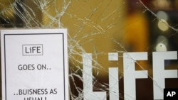 A sign posted outside a looted shop after a night of rioting in and around Manchester, England on August 10.