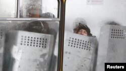 Милиционеры сидят в автобусе пока демонстранты пикетируют здание правительства. Киев, 4 декабря 2013 года.