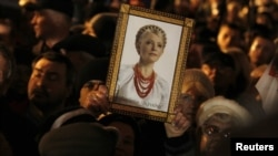 An opposition supporter at a protest rally in Kyiv on November 12 holds up a portrait of jailed opposition leader Yulia Tymoshenko.