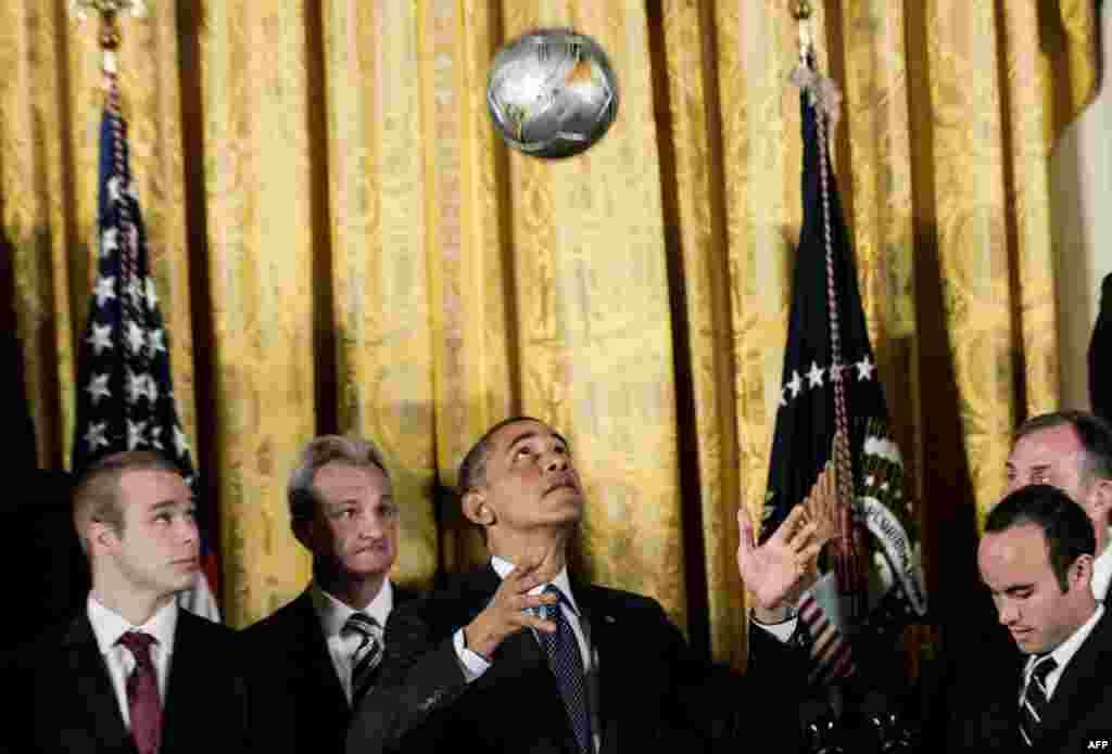 ABŞ-niň prezidenti Barak Obama Ak tamda geçirilen dabarada kellesi bilen futbol pökgisini oýnaýar. Bu dabara 2012-nji ýylyň MLS kubogynyň çempiony Los Angeles Galaxy komandasynyň we 2012-nji ýylyň Stanley kubogynyň çempiony Los Angeles Kings komandasynyň hormatyna geçirildi.(AFP/Brendan Smialowski)