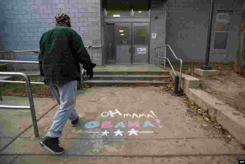 A resident steps over chalk drawings in support of President Barack Obama as he enters a recreation center to vote in South Philadelphia, Pennsylvania.
