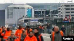 Люди покидают здание аэропорта в Брюсселе, где утром 22 марта 2016 произошли два взрыва