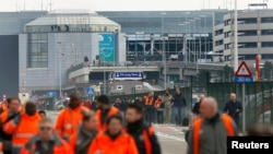 Belgium -- People leave the scene of explosions at Zaventem airport near Brussels, March 22, 2016.